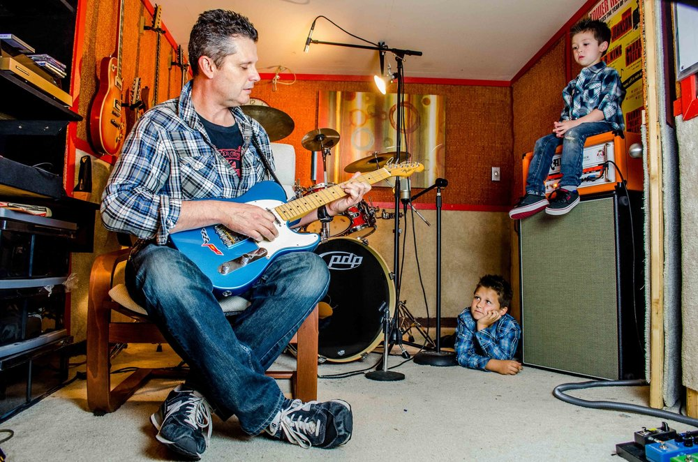 Former Sunday Threads guitarist, Eric Roemheld, left, plays his guitar inside of his homemade studio in Bellflower, Calif., as his sons Jaden, center, and Blake, right, watch on Sunday, March 2, 2014. (Michael Ares / Daily 49er)