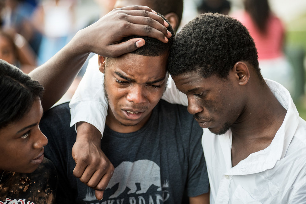 Zhauil Williams, 18, (center) is comforted by Will Miles, 22, (right) during a Tuesday night vigil for 16-year old Asir Brown, their friend who was gunned down by a drive-by shooting a few minutes before midnight on Saturday outside of a Grays Ferry home in Philadelphia. He was pronounced dead on Sunday, July 3, 2016. (Michael Ares / Philadelphia Inquirer)