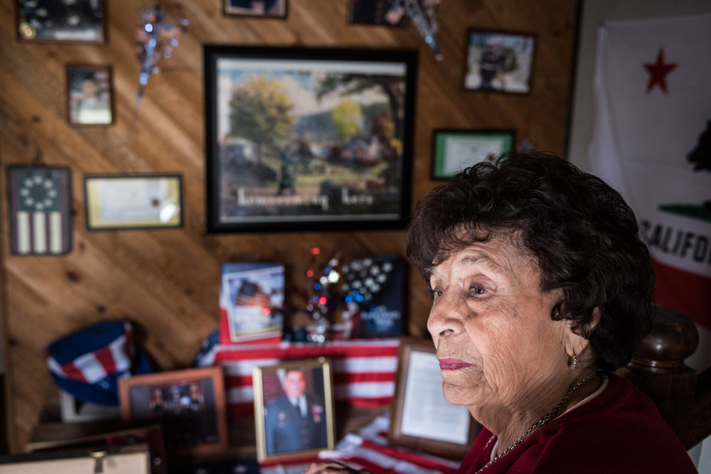 Herminia Casas, a 90-year-old Santa Ana, Calif., resident, sits inside of her home on Wednesday, May 25, 2016, in front of a wall  displaying the military contributions of her husband, brothers, sons, grandsons and great-grandson – a dozen servicemen total. A decade ago, her children helped to mount portraits of the veterans and their certificates of recognition for service across a wall.  (Michael Ares, Contributing Photographer, Orange County Register)