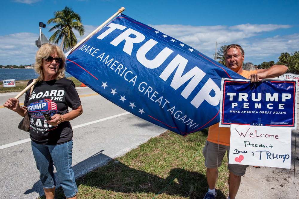 Mary Tulko of Lake Worth, Fla., left, waits in anticipation for the arrival of President Donald J. Trump's motorcade with Miami resident Jerry Swindle, right, on the Bingham Island bridge in Palm Beach, Fla., on Saturday, Mar. 18, 2017. (Michael Ares / The Palm Beach Post)