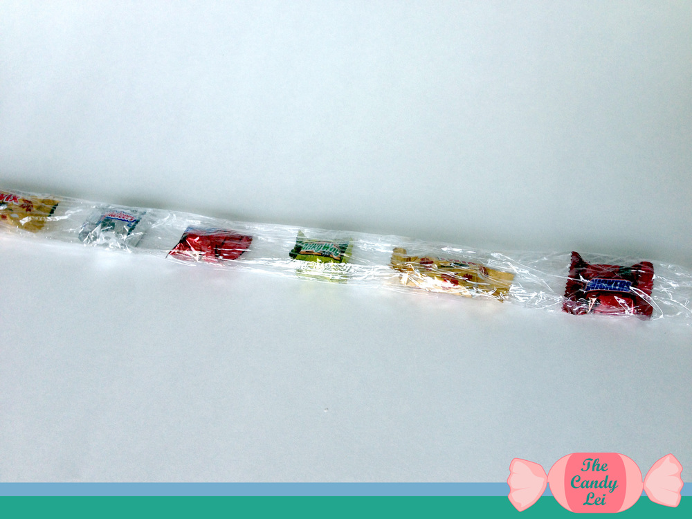 To finish rolling your candy in the plastic wrap use both hands to pinch the plastic wrap around the candy on each end of your row. Now simply roll the entire row up until the plastic wrap is wrapped around all of the candy. You should end up with something that looks like the image above.