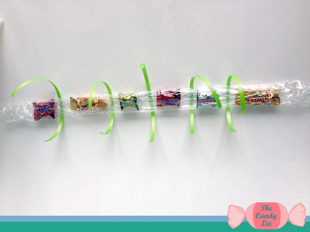 Slide each piece of ribbon underneath the plastic wrap in the open space between each candy. Tie a simple knot and pull it tight. Try to keep an even amount of ribbon on each side of the knot as seen in the image below.