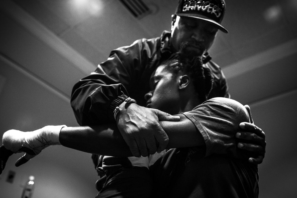 Coach Jeff helps Tiara stretch before her professional debut fight.