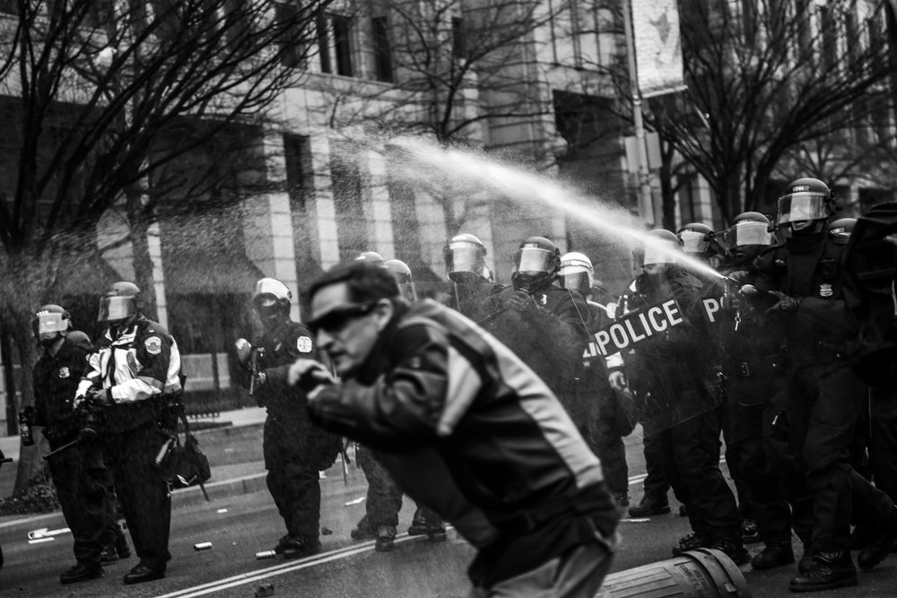 Police officers wearing riot gear spray protesters with pepper spray on K St. N.W., hours after President Trump was sworn in as the 45th US President.