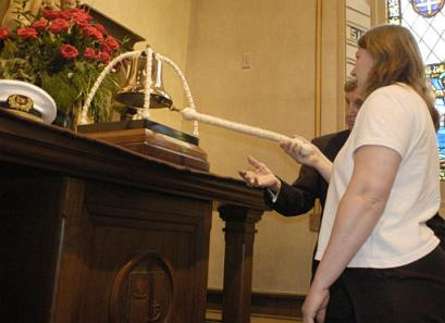 Heidi rings the bell in honor of her father at a memorial service at Mariner's Church in Detroit, Michigan.