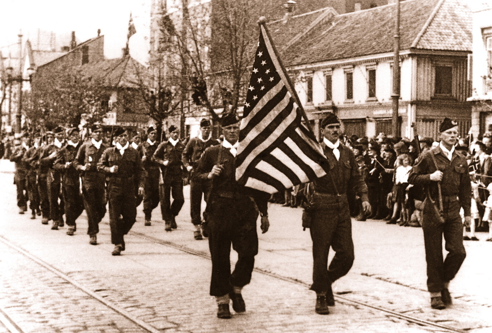May, 1945: U.S. paratroopers march the Ericksons' 48-star flag down a street in Trondheim, Norway following the city's liberation from German occupation.