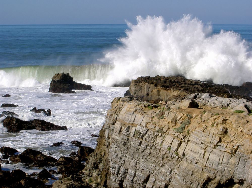 At Pescadero Beach, a plunging breaker  crashes against the rocks .