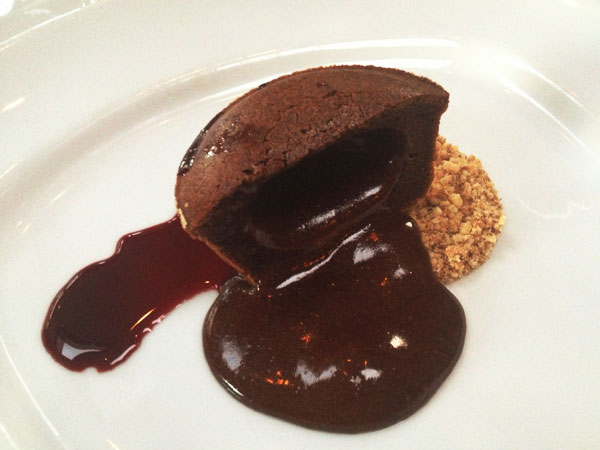 Light Bistro - Warm Chocolate Cake filled with chocolate sauce and served with crushed walnuts and grape syrup