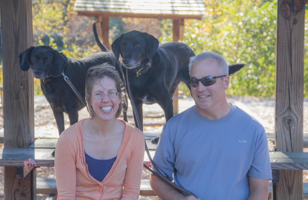 Family portrait with two black labs