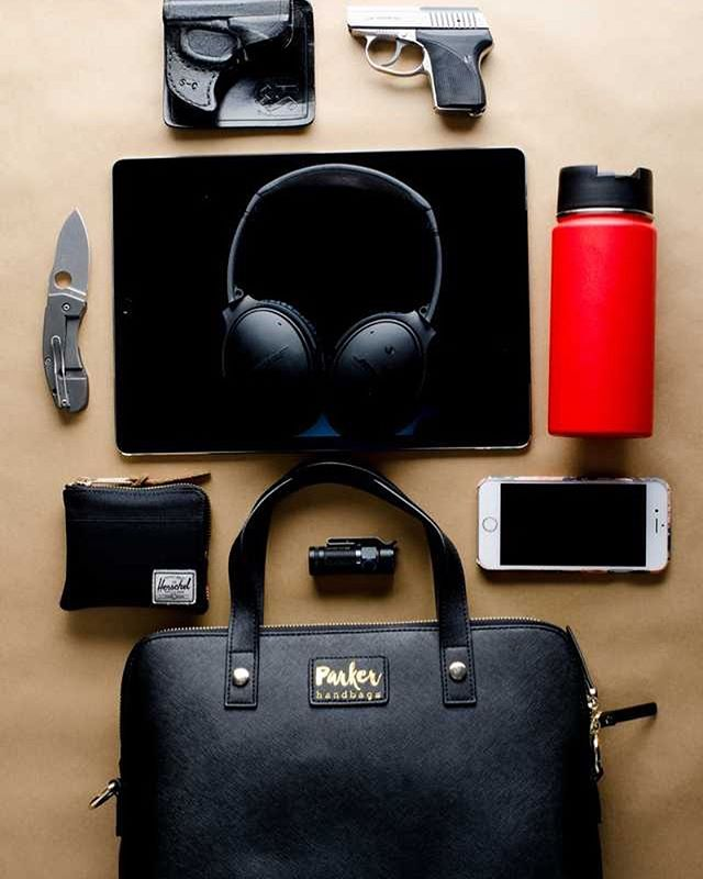 """Parker Handbags is the perfect size for the essentials. With so many different needs a handbag must fulfill, versatility is by far one of the most important duties when life demands so much from us. This is the """"I have to get sh!* done!"""" bag combination, featuring iPad Pro, Bose headphones, hydroflask travel coffee cup, wallet, phone, personal safety devices and flashlight. #parkerhandbags #safetyfirst #girlswhocarry"""