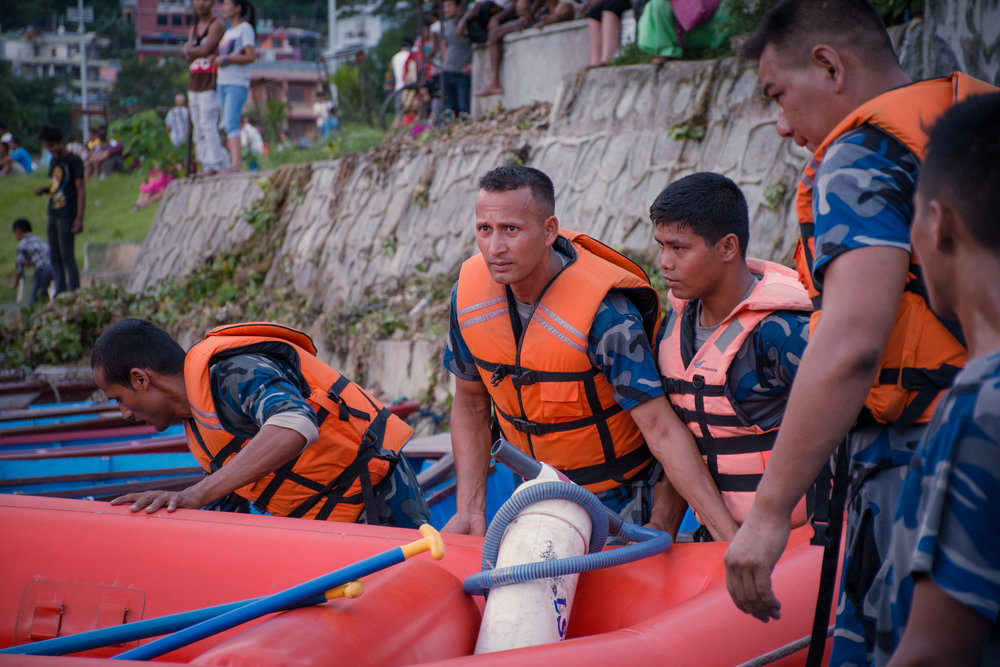 Rescuers solemnly prepared to enter the lake to look for the bodies of two Nepali people.