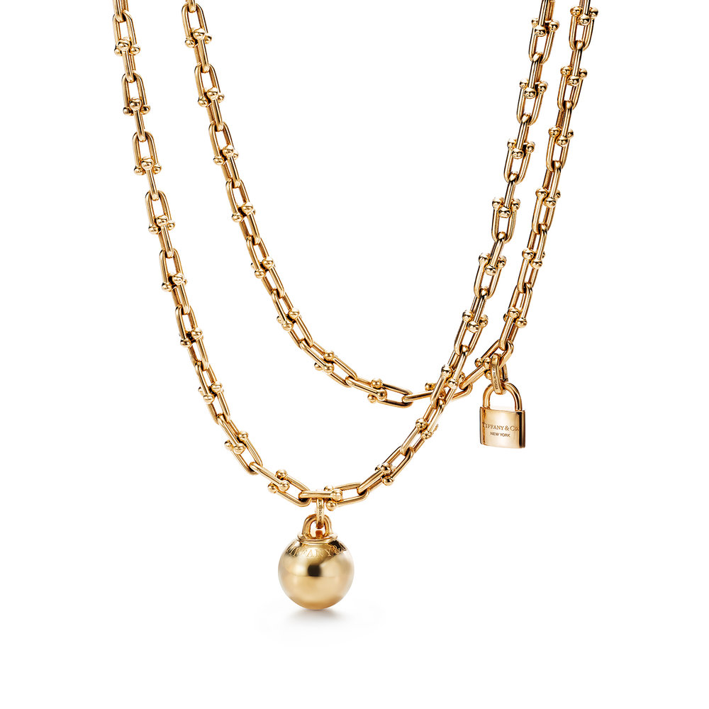 18k gold necklace with ball, chain and locket detail.