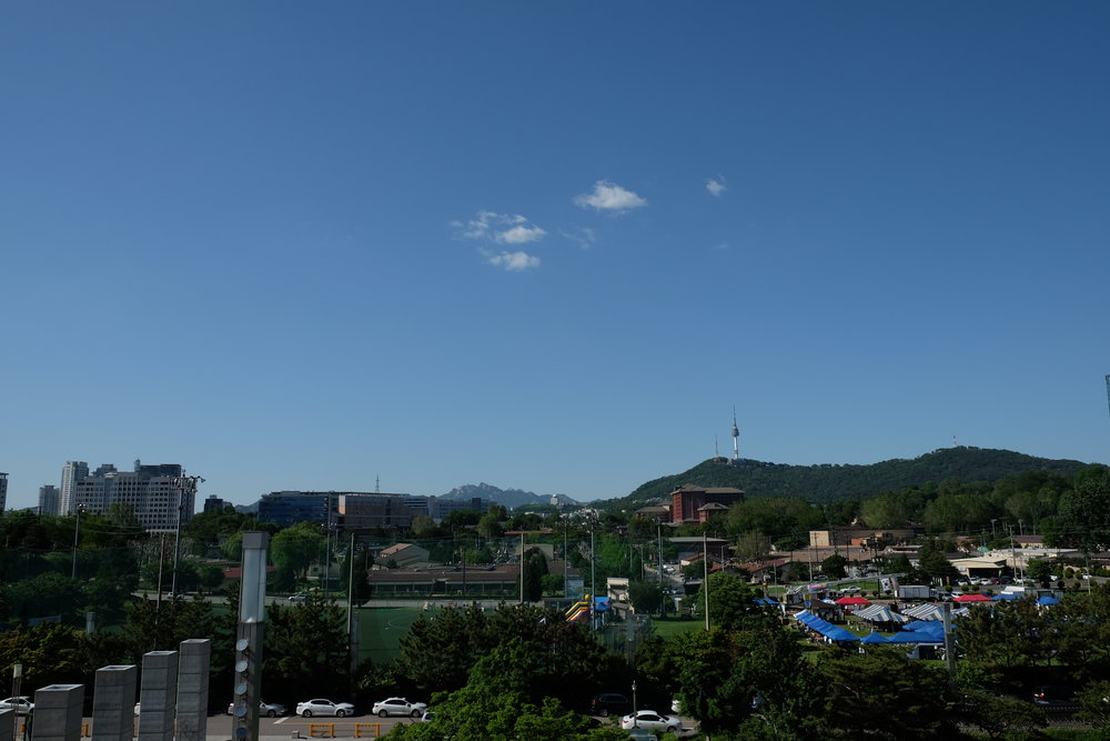 If you keep walking past the main building through the courtyard, you come across a balcony that offers views of N Seoul Tower and the surrounding mountains beyond the city.