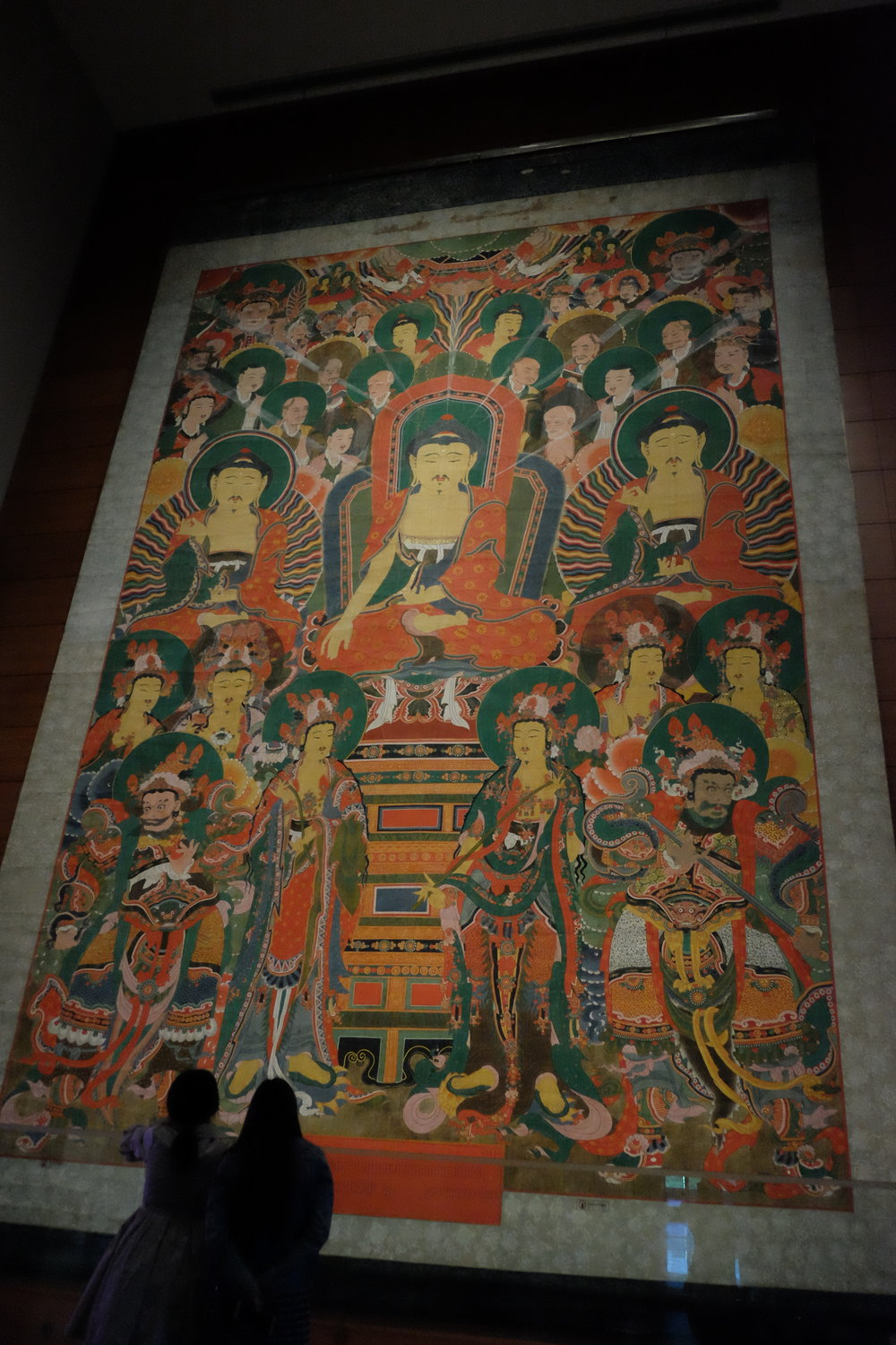 """When we were there, the """"Gathering of the Three Buddhas"""" exhibition was going on and boy, were we glad to see it. Normally hung in Yongheungsa Temple, this large-scale Buddhist hanging scroll depicts depicts a gathering of Śākyamuni Buddha, Bhaisajyaguru Buddha, and Amitābha Buddha hosted by Śākyamuni Buddha, the ruler of the secular world. People prayed to these three Buddhas for a long life free from illness, and hoped for a rebirth in the Western Paradise. To illustrate how tall it is, see the two women in the lower left for scale."""