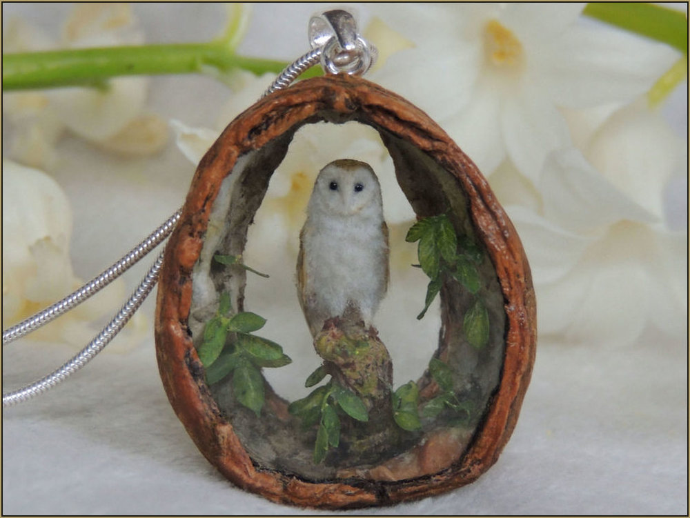 A high detailed miniature barn owl set inside a pendant made from English walnut shell finished with a hallmarked sterling silver hoop bail. Both the front and back apertures are sealed with hand cut crystal glass. The interior is decorated with hand painted miniature walnut leaves.    The barn owl Sculpture has black polished glass eyes and plumage made from plant fibre and hand painted naturally moulted feathers.    Arranging the unique design for the pendant, its components and pose of the sculpture is determined by working with the natural shape and intricacies of the walnut shell.       Measurements : 3.5 cm at the highest point (excluding bail), 3.2 cm across the widest point 1.2 cm Depth.    Prices for a similar work start from £120.00 - £210.00 depending on the size and design of the pendant. Prices including postage within the UK.    Design by Anya Stone