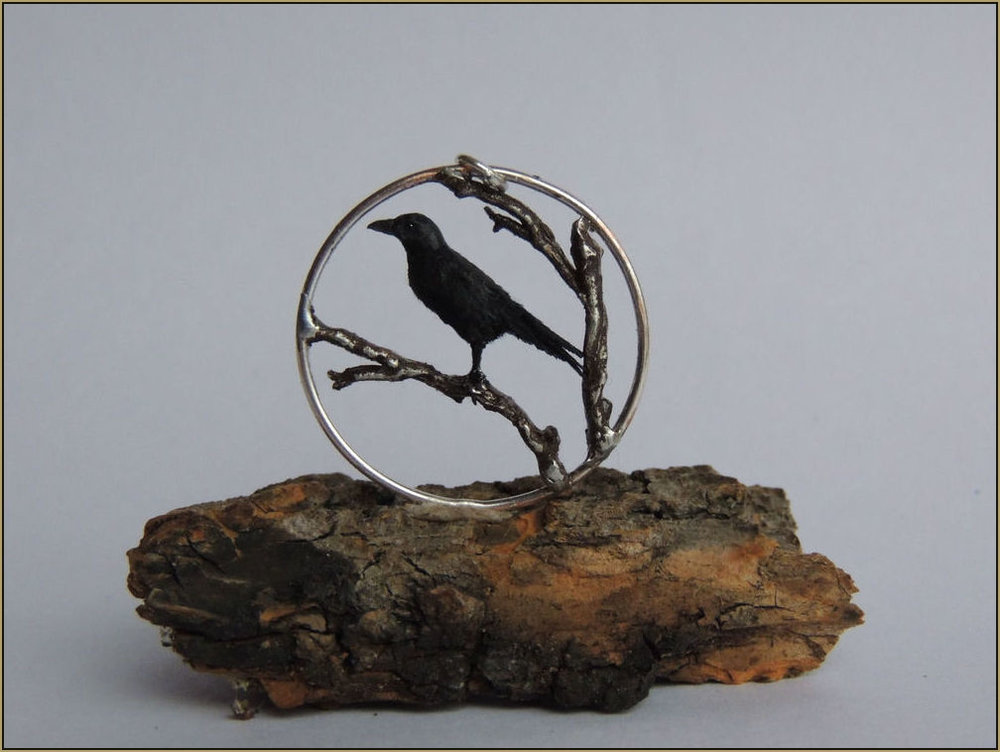 Crows have very strong connections to their family and are said to be monogamous birds. Because of this in ancient Egypt they were symbols of faithful love, and in ancient Greece the crow was seen as a symbol of success. In India the crow is considered auspicious bringing good luck.  Medium: Stainless steel talisman & pewter branch, polymer clay and fiber crow sculpture with glass eyes.  Dimensions: 2.5 cm diameter  Year: 2013