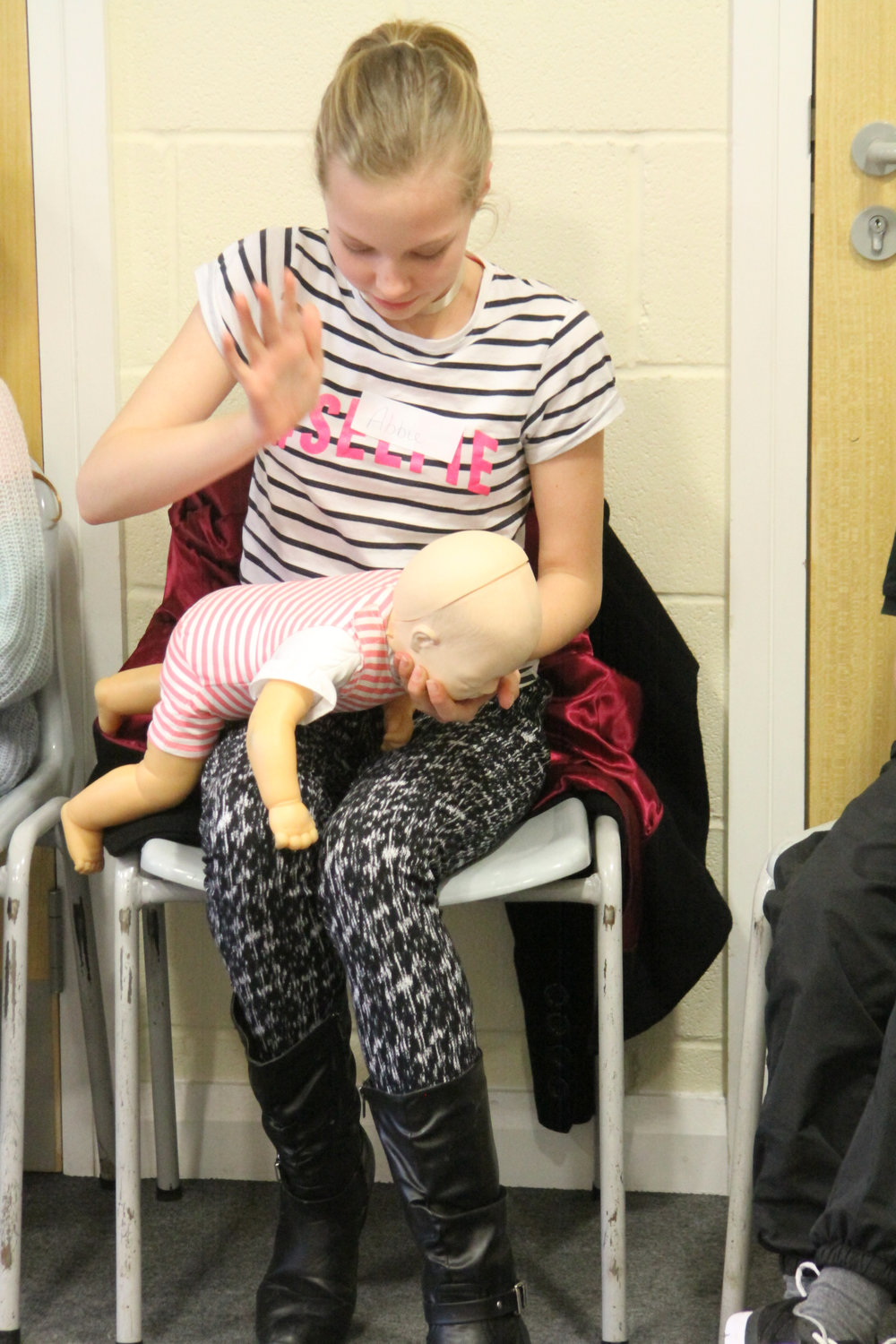 Abbie (11) practising what to do with a choking infant.
