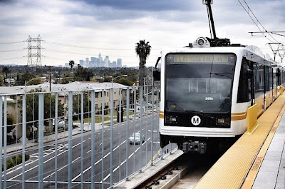 An Expo Line test train rests at the La Cienega station, with the downtown L.A. skyline in the distance. Photo by Steve Hymon/Metro via Wikipedia.