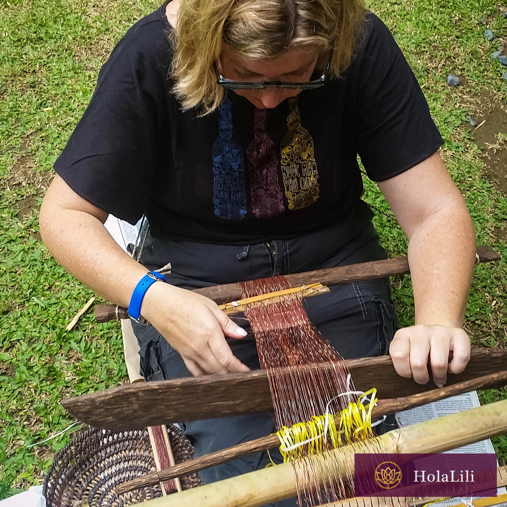 Meg, trying her hand at weaving in a weaving class.