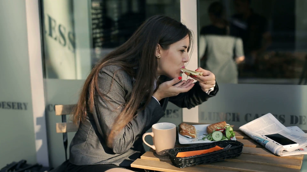 businesswoman-eating-lunch-and-drinking-coffee-outside-the-cafe_4jvogiux__F0000.png