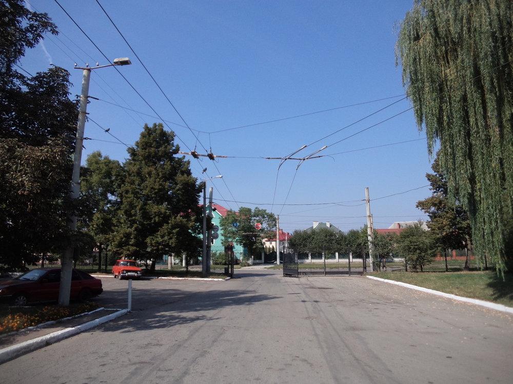 Místní vozovna trolejbusů má dvě brány, obě přitom směřují na tutéž ulici, příznačně nazvanou Trolejbusna. Na tomto snímku je zachycena hlavní brána (vrátnice se nachází zhruba pět metrů vpravo od pozice fotografa)– pokud trolejbus zabočí doleva, bude směřovat k centru města, a pokud by mohl zabočit doprava (v tomto směru stopa chybí), míjel by druhou bránu a dostal by se na nedalekou konečnou linky č. 5. KP Elektroavtotrans.