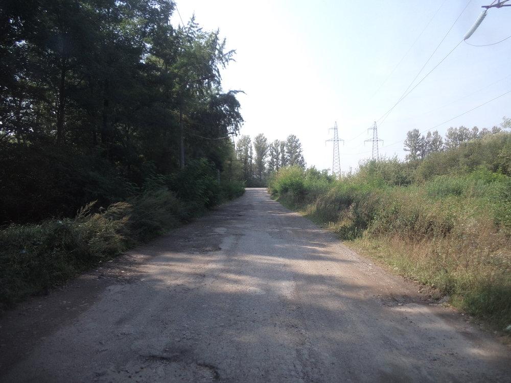 V dáli lze zahlédnout silnici H09 Ivano-Frankivsk – Lvov a k ní směřující rozbitá cesta je...