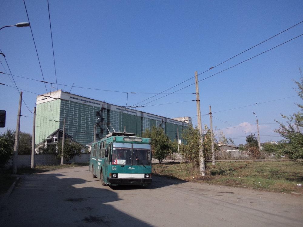 """Konečná linky č. 2 Vulycja Junosti se nachází na jihovýchodním okraji Ivano-Frankivksa, jmenovitěv oblasti místní průmyslové zóny, které dominuje """"Kombinat chliboproduktiv"""", jenž za fotografem zvěčněným trolejbusem typu JUMZ T2 vytváří objemnou kulisu. Obytná zástavba je v těchto místech velmi řídká."""