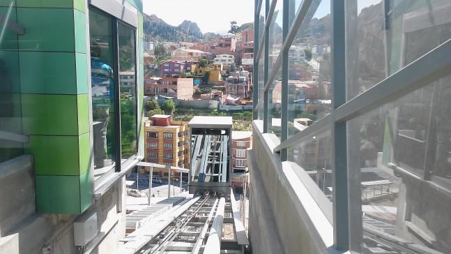 """Pozemní lanová dráha otevřená dne 3. března 2015 usnadňuje přístup ke stanici zelené linky Alto Obrajes z ulice 17 de Obrajes položené níže. Bezplatná cesta na trase o délce 74 m trvá 38 sekund. Nicméně se nejedná o jedinou pozemní lanovku ve městě, už roku 2003 byla totiž zprovozněna jiná, obsluhující tamní muzeum Kusillo.Tento starší """"bratr"""" na vzdálenosti o délce 48 m překonává 38m výškový rozdíl a je nejvýše položenou pozemní lanovou dráhou na světě, když leží v nadmořské výšce zhruba 3 600 m n. m.(novápozemní lanová dráha u stanice Alto Obrajes je položena o více než100 metrů níže). (foto: Empresa Estatal de Transporte por Cable """"Mi Teleférico"""")"""