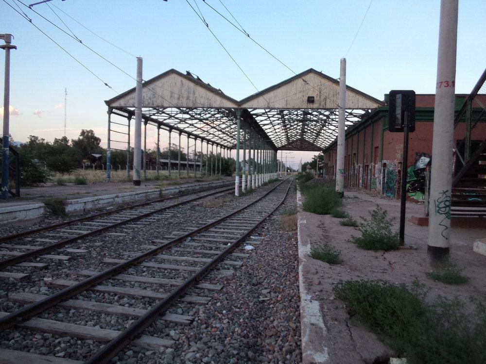 Průjezdné nádraží Mendoza patřilo dráze zvanéFerrocarril General San Martín (rozchod 1 676 mm). Končily zde mimo jiné i vlaky z Buenos Aires, ze kterého se sem dalo dostat z obou možných směrů, neboť Mendozu obklopoval jakýsi železniční okruh, jak už ostatně vyplynulo z jednoho z předchozích komentářů. Zaústěna sem byla i větev dráhy Ferrocarril General Belgrano (rozchod 1 000 mm), byť hlavní stanice této dráhy byla v Mendoze (přesněji řečeno na území Gran Mendozy)někde jinde, a sice asi 3 km východně od této (tj. napravo od snímku).