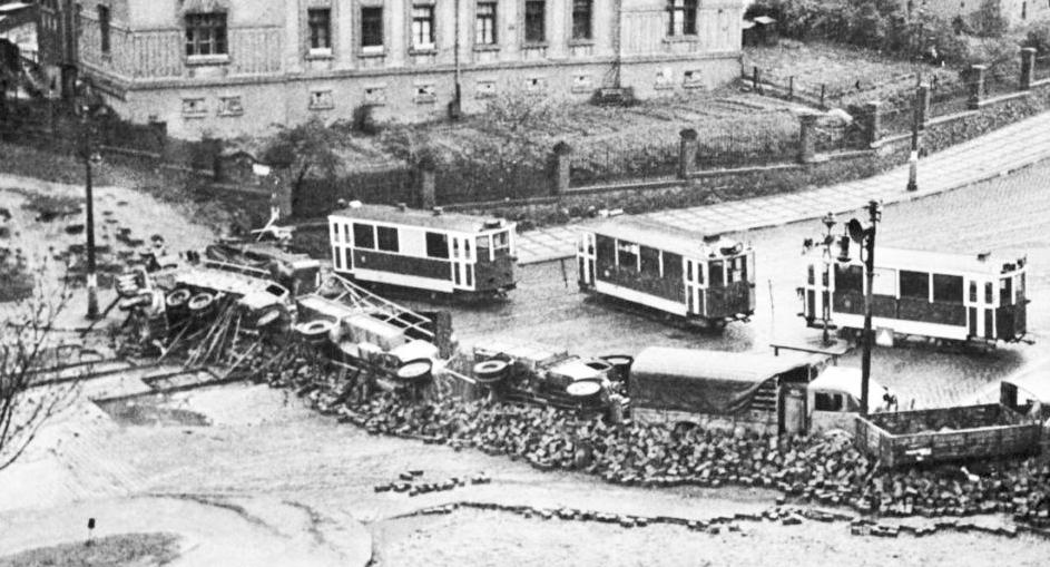 Auta položená na bok, vlečné vozy tramvaje postavené napříč ulicí. I tak vypadaly pražské barikády.