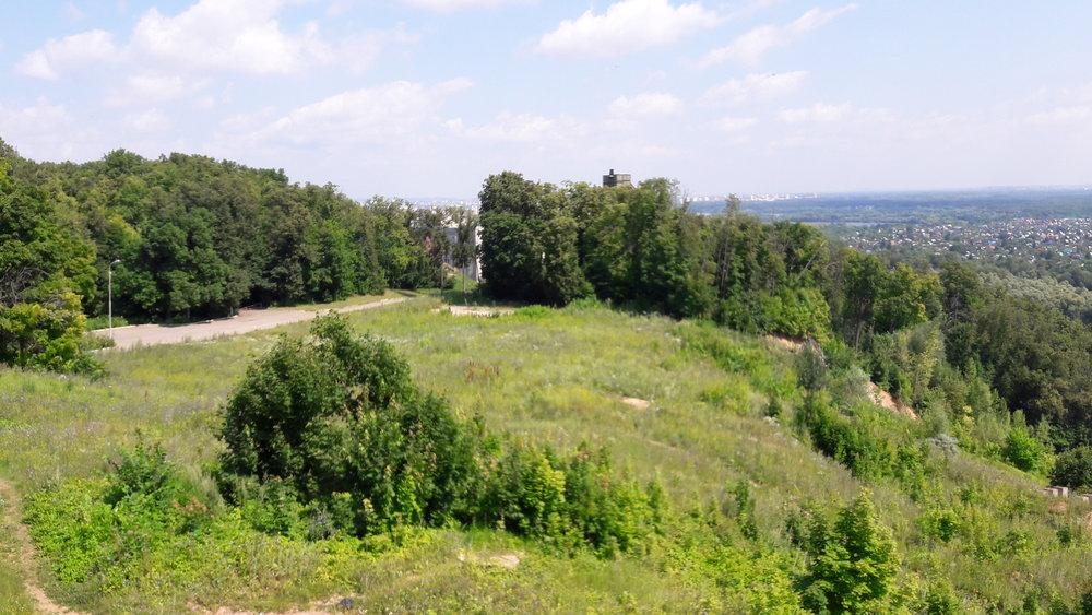 Na tomto snímku pořízeném z kabinky lanové dráhy blízko horní stanice jde vidět vrchol starého skokanského můstku a také provozní budovu, ve které mají sportovci zázemí.