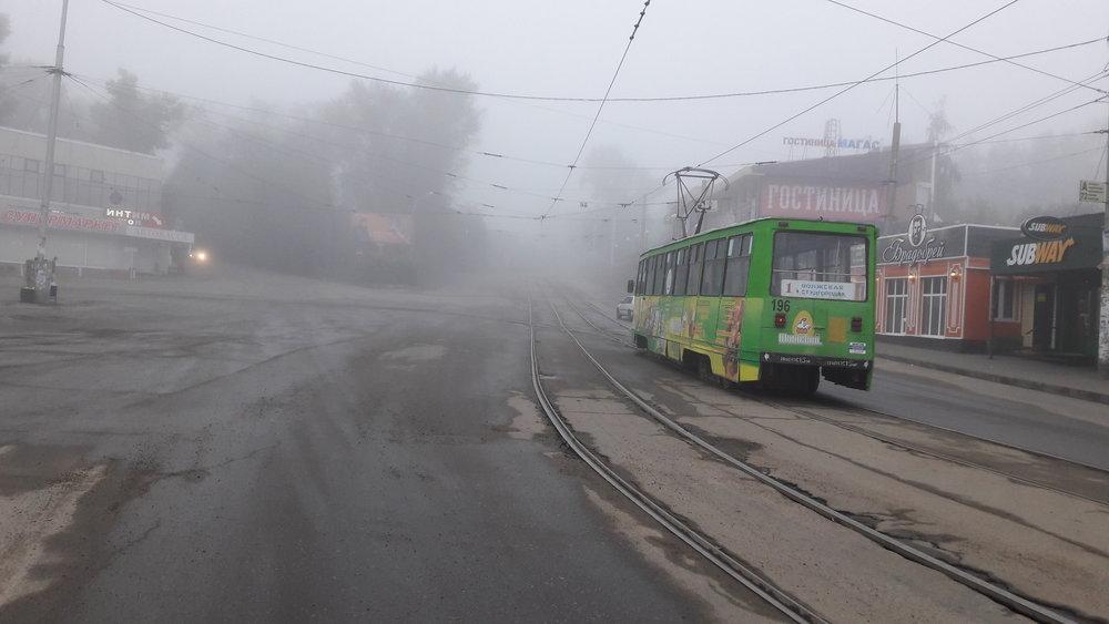 Tramvaj v ranní mlze u vlakového nádraží.
