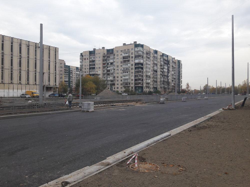 Procházka od Irinovskogo prospekta k prospektu Kosygina po prospektu Nastavnikov. Zde pohled směrem na sever. Tam, kde končí sloupy, jsou položeny dvě výhybky pro obrat  čižiků , kteří sem začnou jezdit ještě v tomto roce. Tramvajová trať, po které jezdí městské tramvaje linek 7 a 10, není na snímku příliš vidět, je totiž v pozadí, brzy ale začne být také přestavována.