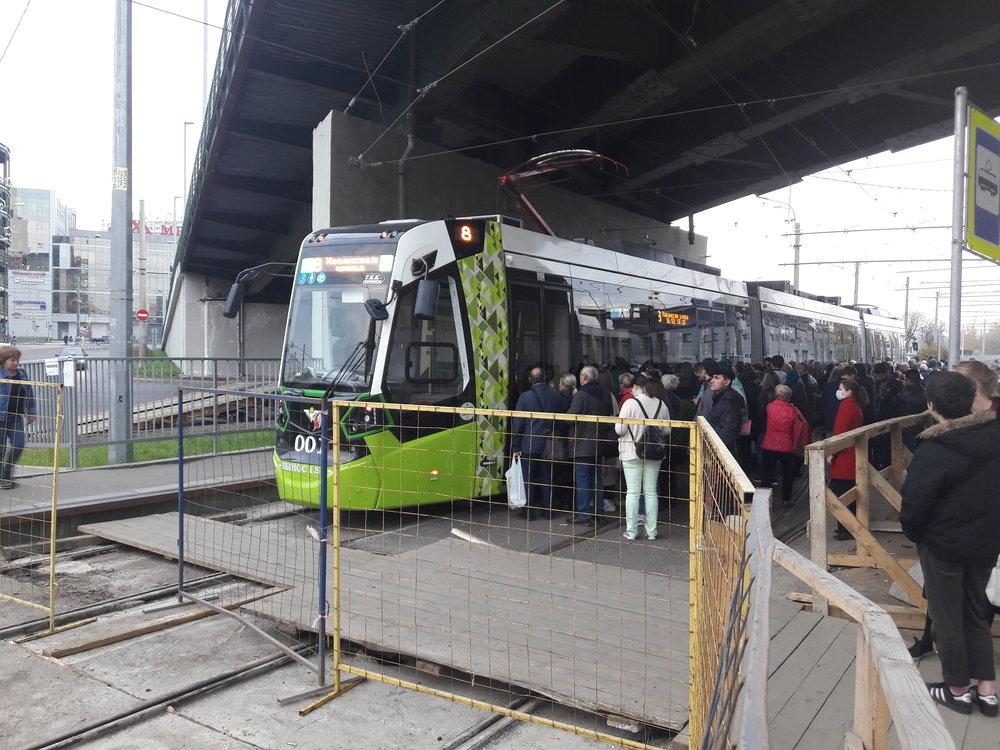 Lidé vystupují jednou stranou, poté přejde řidič do druhé kabiny, a otevře dveře novým cestujícím, kteří čekají na straně druhé.