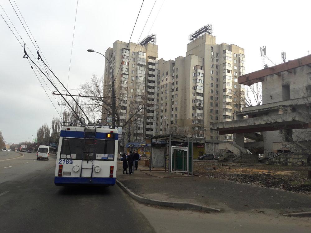 Nástupní (a také občas i výstupní) zastávka konečné Universitatea Agrară na severozápadě města. Pohled směrem do centra poté, co se trolejbus přes cestu obrátil a projel i smyčkou (viz další obrázek). Podivných objektů, jako je ten vpravo, má Kišiněv docela dost.