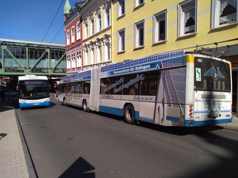 Na snímku vidíme na pravé straně trolejbus, který přijel ze Solingenu. Zahne doprava a pak doleva, aby dojel k vohwinkelskému nádraží. Sběrače – v souladu s tím, co bylo psáno o několik snímků dříve – shodil ještě před příjezdem na blokovou smyčku: musel, na snímku viditelná stopa je totiž určená pouze protisměrně jedoucím trolejbusům. Ty se ale natrolejují těsně před výjezdem ze smyčky.
