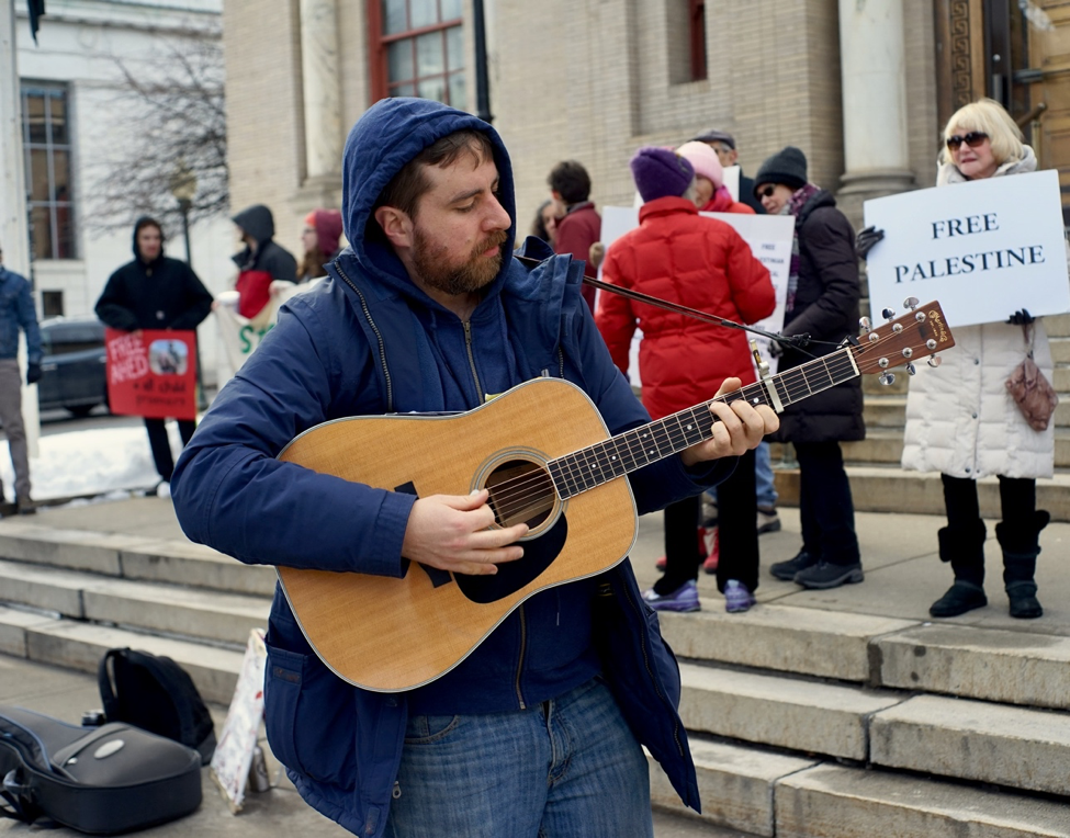 The rally was joined by an acoustic performance by Ben Grosscup, who performed his original songs in solidarity with the plight of  Tamimi  and other Palestinian child prisoners.