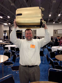 Brian Jensen hoists his Pressure Chamber winner's trophy, a golden suitcase.