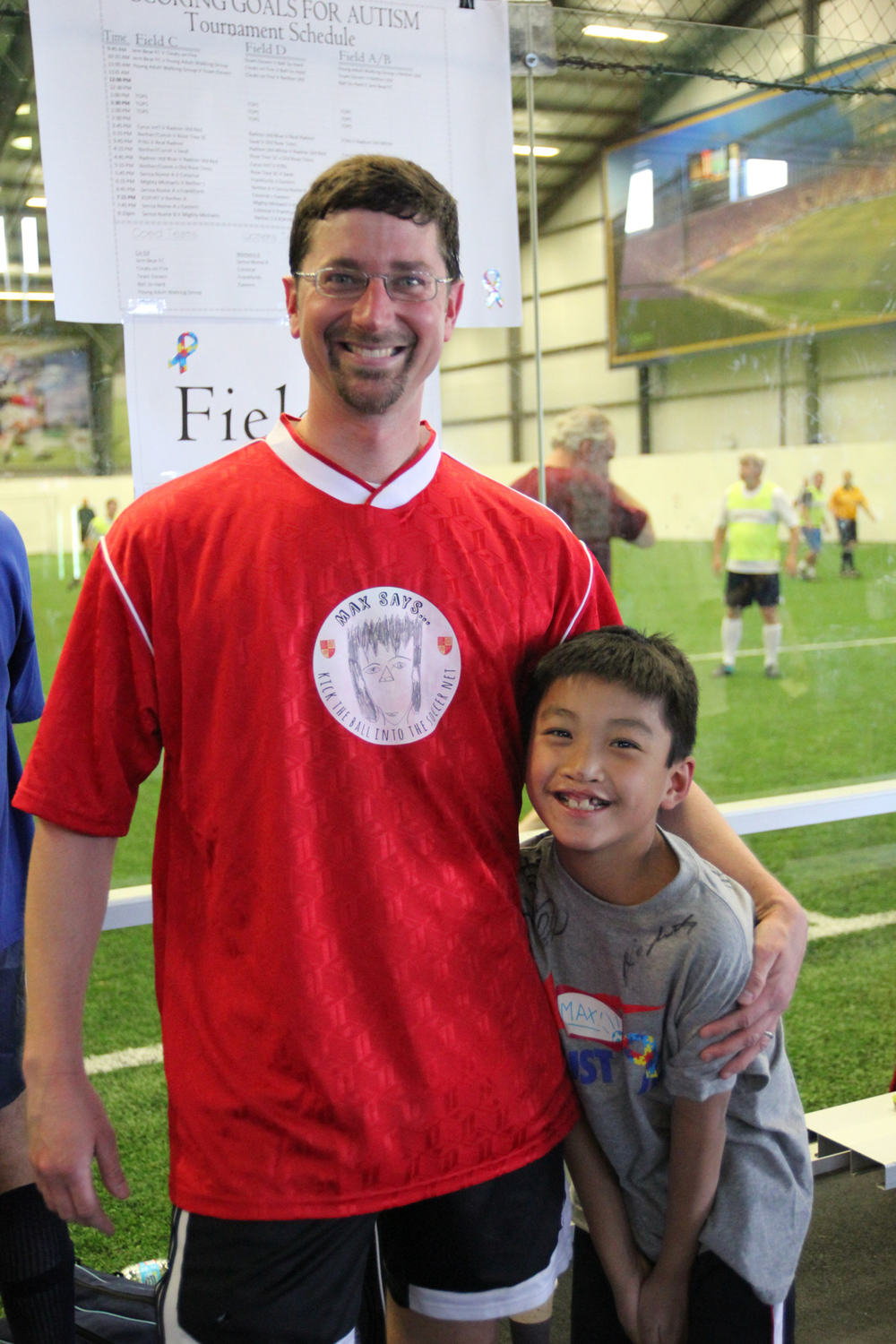 Kevin pictured at a charity soccer tournament with his son, Max, sports a jersey logo designed by Max.