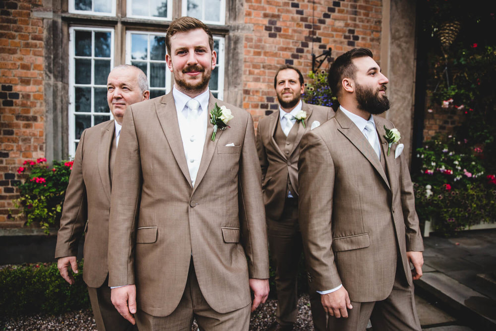 groomsmen posing at pillared entrance