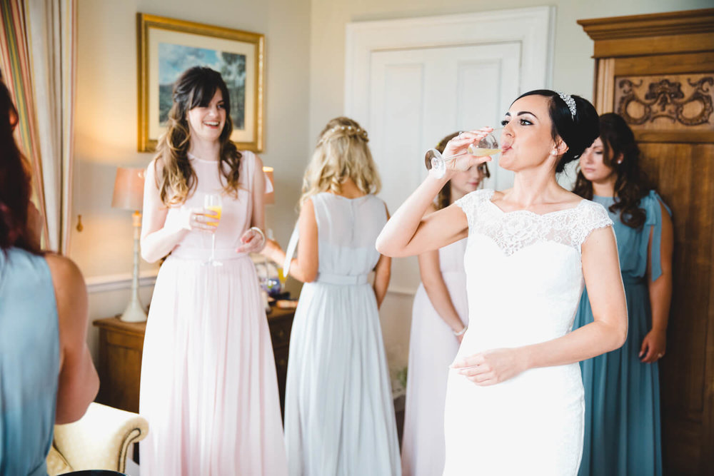 bride enjoying a drink with bridesmaids