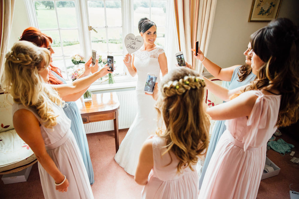 bridesmaids photographing bride in window with mobile phones
