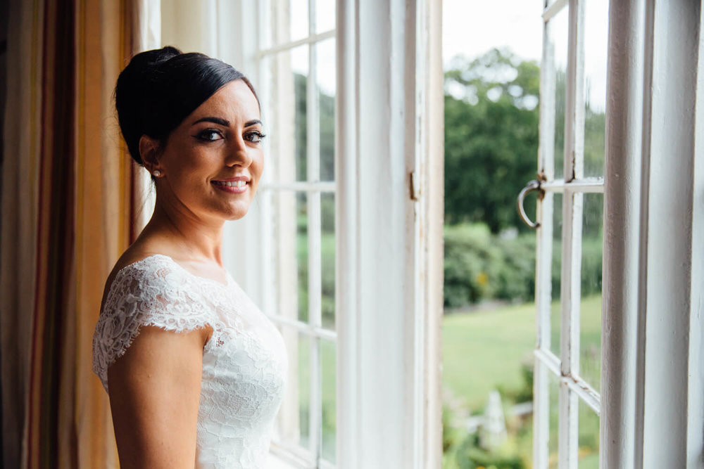 bride portrait at window looking into camera