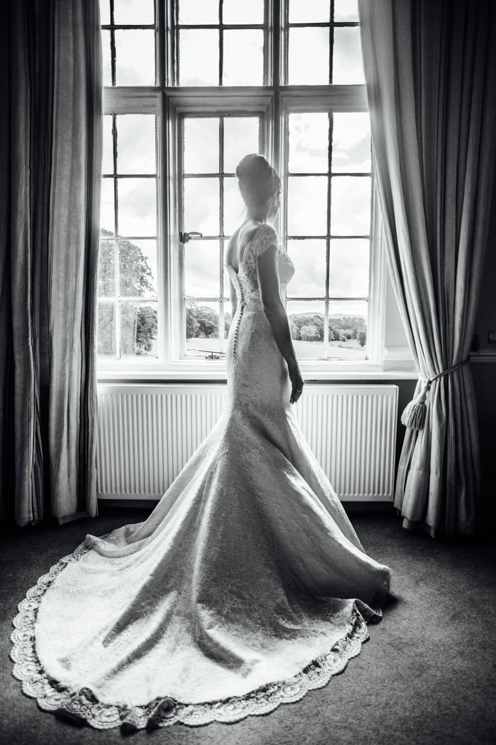 full length black and white photograph of bride in window