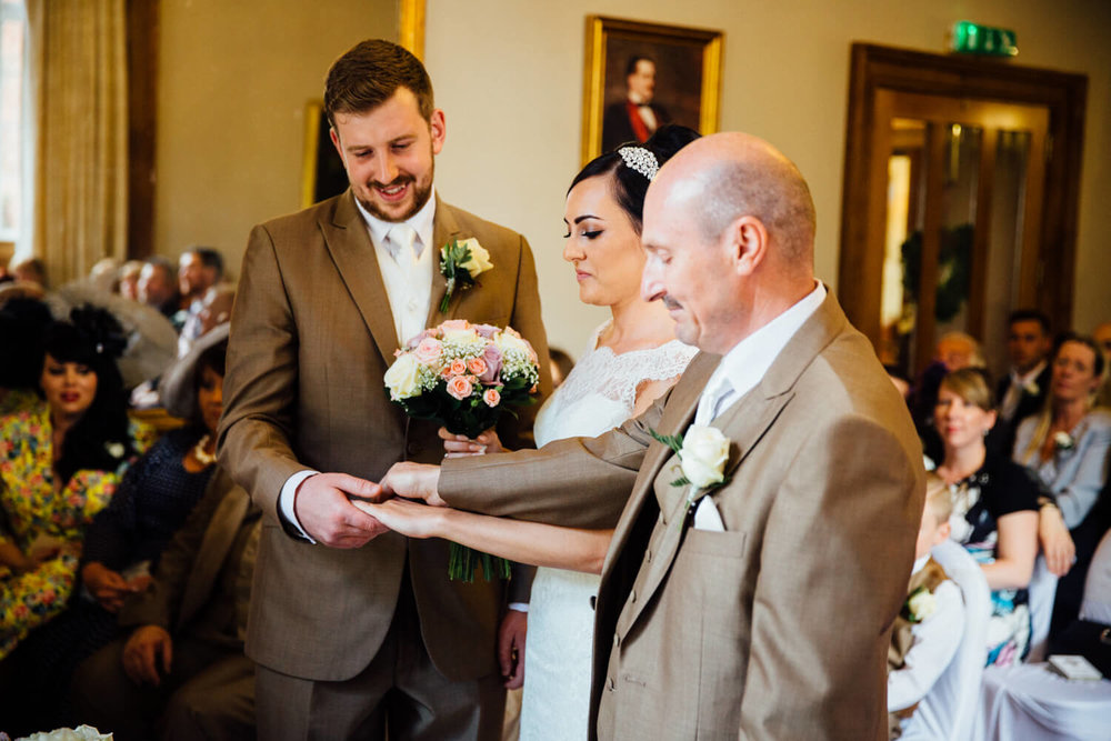father of bride holding hands with groom