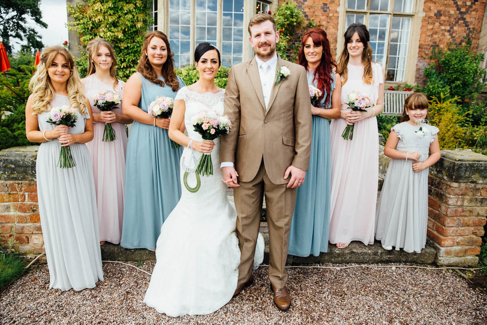 bridal party with groom in grounds