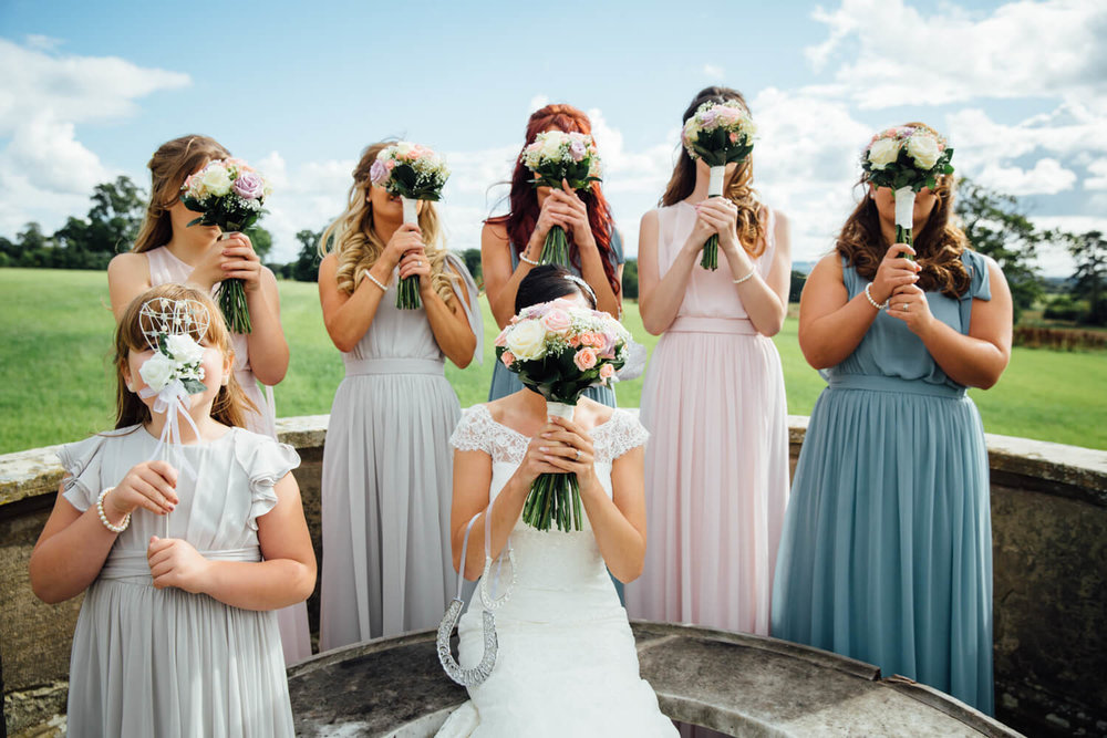 flowers held to faces of bridal party