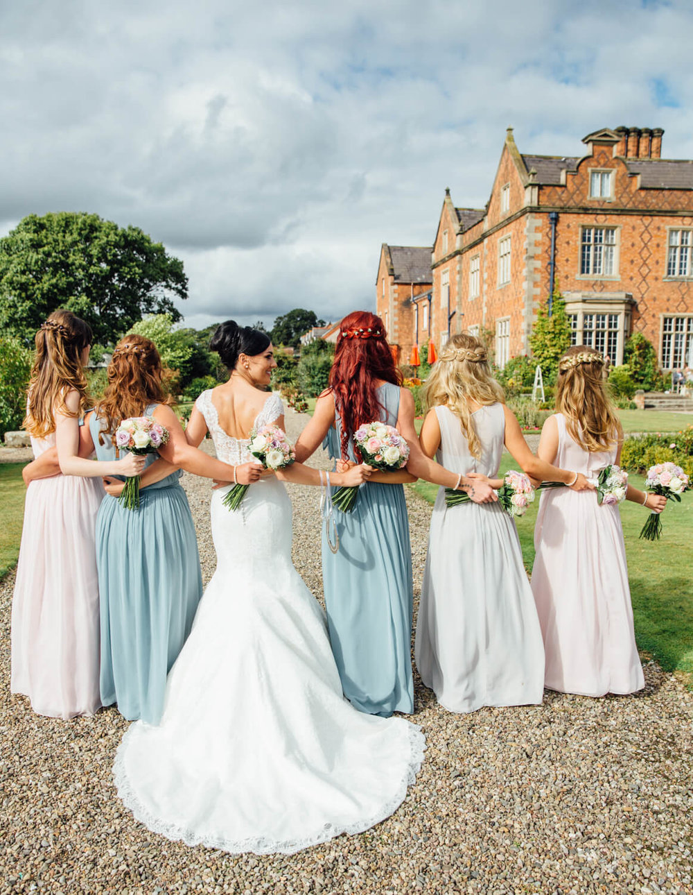 bride and bridesmaids with back to camera linking arms