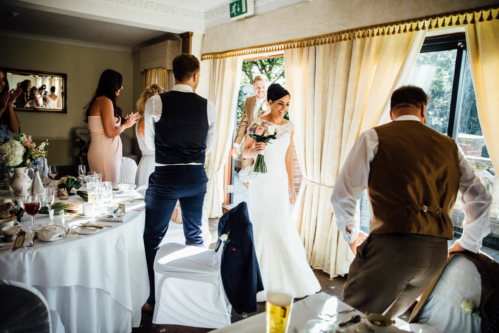 bride enters wedding breakfast room