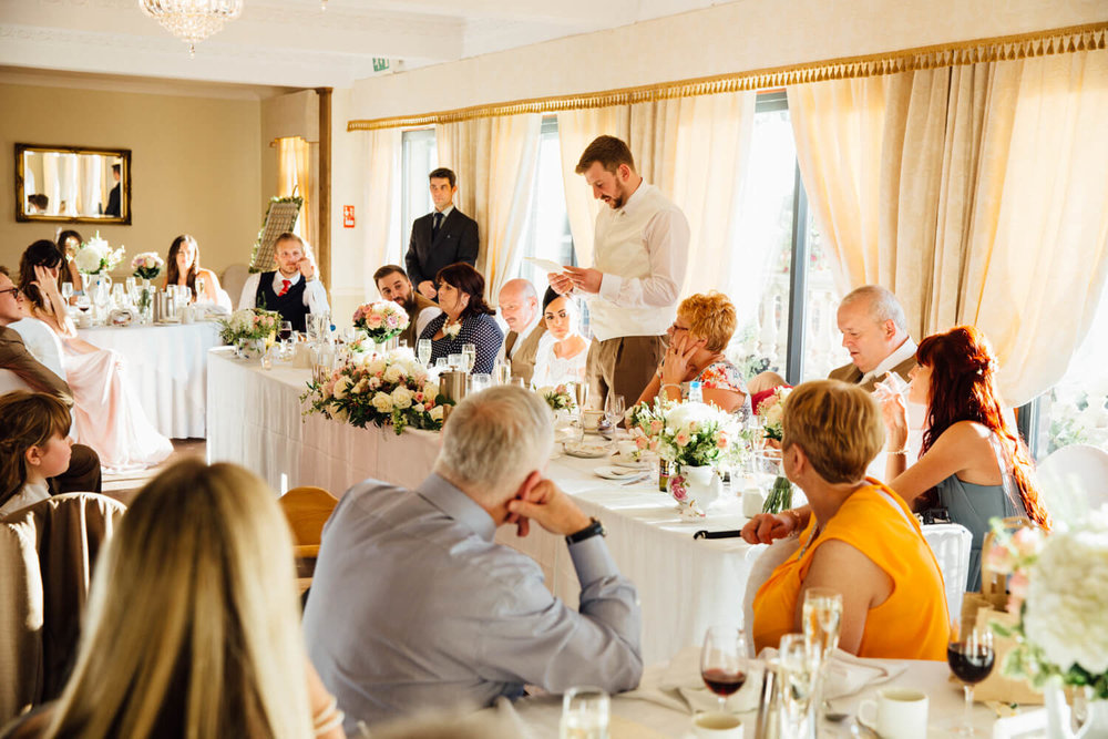 groom gives speech to wedding party